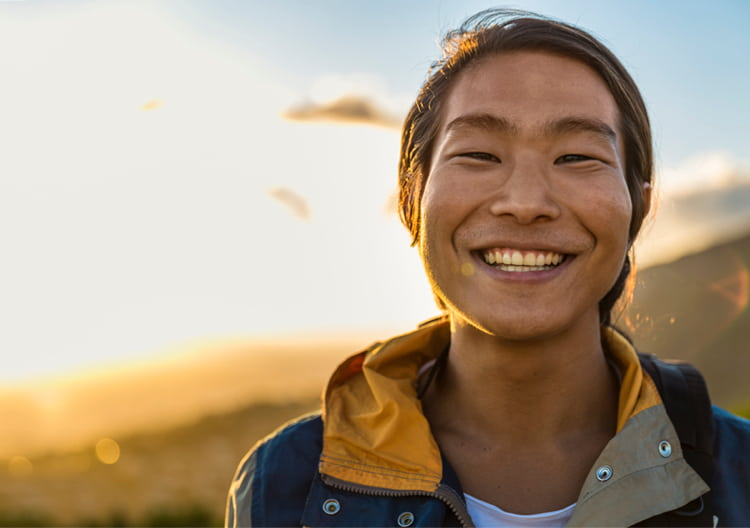 A young man smiling at the top of a mountain with the sun at his back.