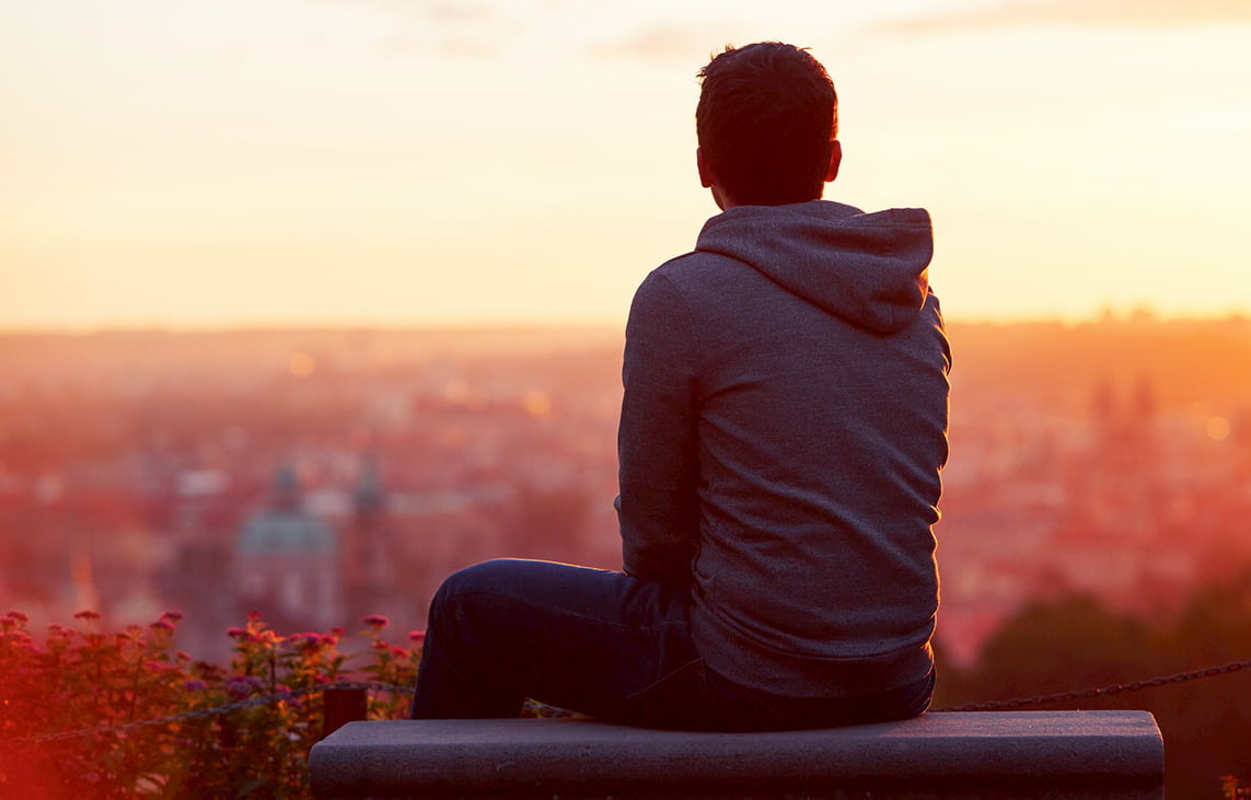 A young man sits on a hillside wall overlooking a city at sunset | Newport Institute