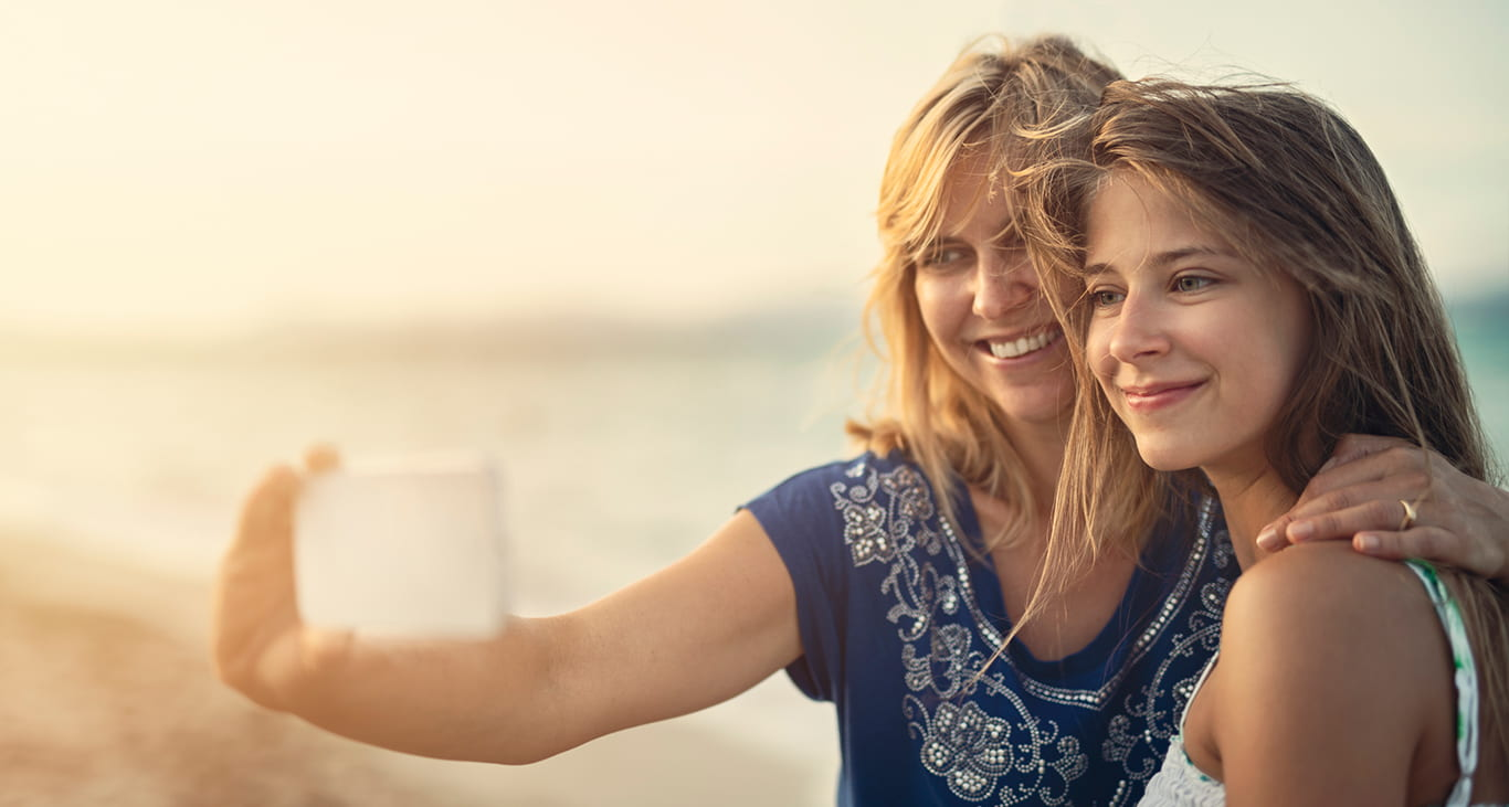 A mom and daughter taking a selfie together on a beach