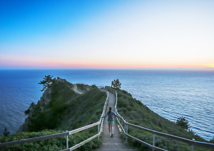 Young woman running along a path out on a rock outcrop along the Pacific Ocean at sunset.