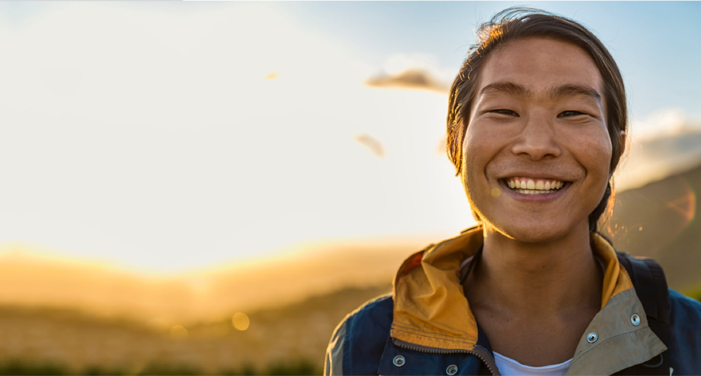 A young man smiles with the sun on his back on a remote hilltop.