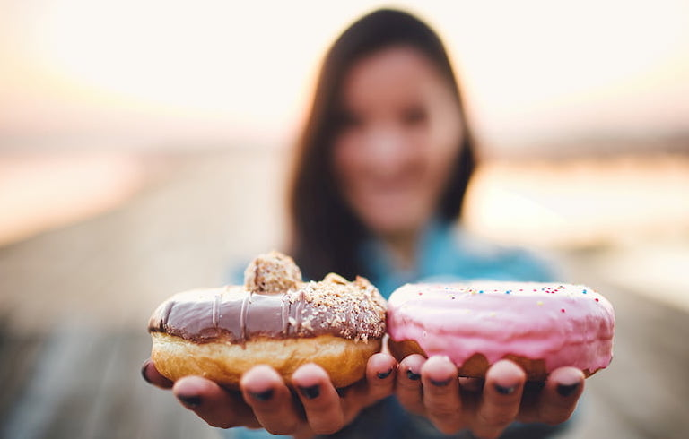Young woman holding two donuts | Newport Institute